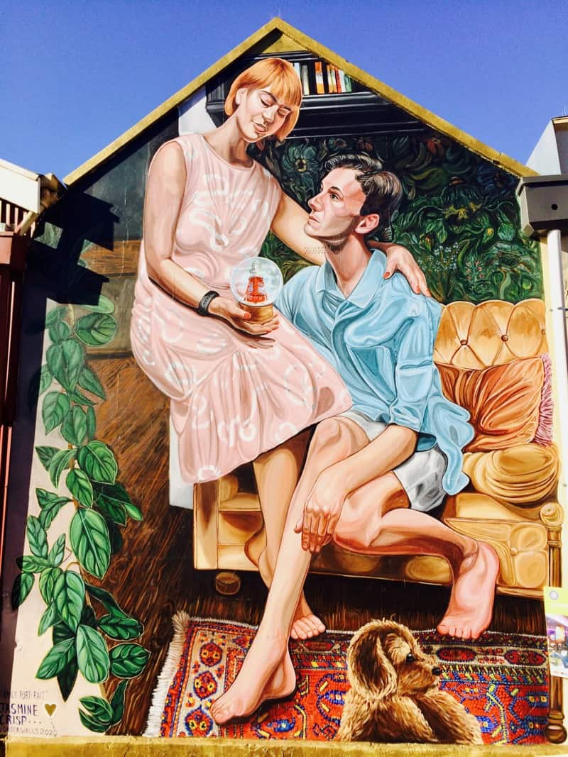 Wonderwalls Port Adelaide Mural holding a snow globe with the Port Adelaide Lighthouse