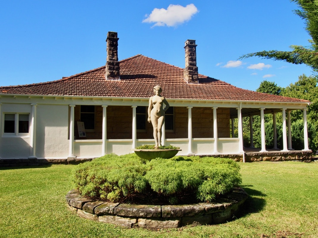 Sculpture modelled on Rose by Norman Lindsay next to House